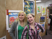 shelby and sarah pose with their art work